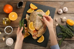 Woman adding rosemary to raw chicken with orange slices at wooden table, top view