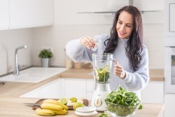 Woman adds water into a mixer for a spinach, banana, and apple smoothie.