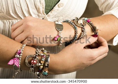 Woman adjusting bracelets  #345470900
