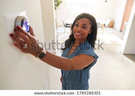 Woman Adjusting Digital Central Heating Thermostat At Home Foto stock ©