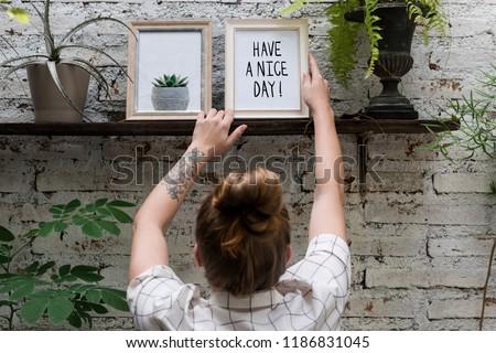 Woman adjusting Have a nice day photo frame on shelf