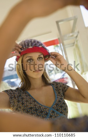 Woman adjusting knit cap in front of mirror at store