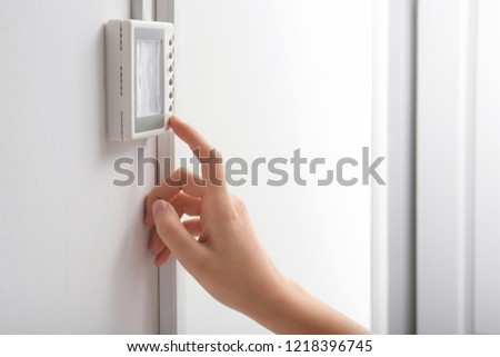 Woman adjusting thermostat on white wall, closeup. Heating system