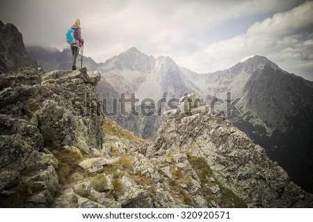 woman adventure hiker on mountain summit