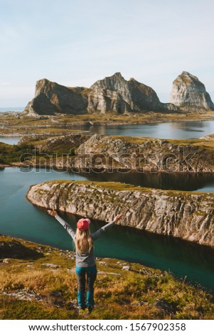 Woman adventurer raised hands traveling in Norway mountains rocks and sea view adventure vacations healthy lifestyle success motivation Helgeland islands landscape