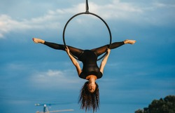 Woman aerialist performs acrobatic element split in hanging aerial hoop against background of blue sky and white clouds.
