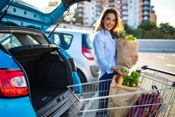 Woman after shopping in a mall or shopping centre and driving home now with her car outdoor. Woman shopping in a grocery store/supermarket, putting the groceries into her car in the parking lot