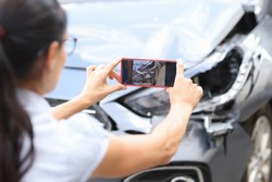 Woman agent takes pictures of damage to car after accident by smartphone