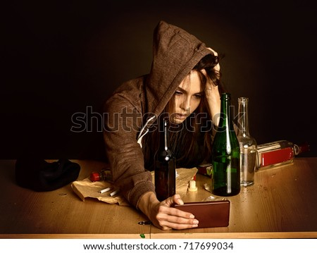 Woman alcoholism is social problem. Heavy parting with a guy. She in hood and hat with green alcohol bottle in bad mood . Drunken woman falls asleep on dirty table black background. Сток-фото ©