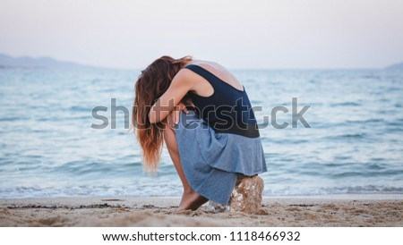 Woman alone and depressed sitting at the beach #1118466932