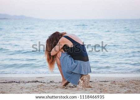 Woman alone and depressed sitting at the beach #1118466935