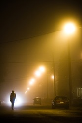 Woman alone in the middle of the foggy street