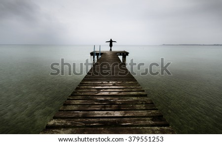 Woman alone on the pier near the sea and looking on the water with arms outstretched #379551253