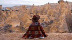 Woman alone with the volcanic landscape at Devrent Valley in Cappadocia. Girl walking around Fairy chimneys surronded by tufa formations at Imaginary Valley in winter season in Cappadocia, Turkey.