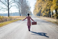 Woman alone with vintage suitcase hitchhiking on empty road