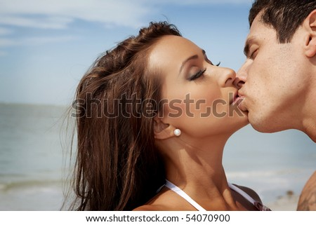 Woman and a man kissing at a beach