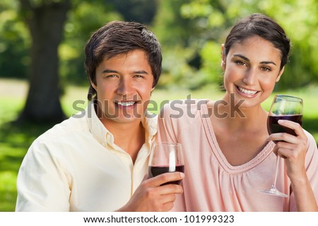 Woman and a man looking straight ahead while holding glasses of red wine in a park