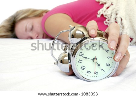 Woman and alarm clock in bed