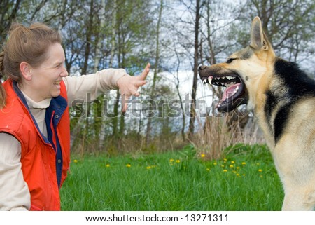 Woman and alsatian dog making faces to each other