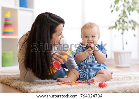 Woman and baby playing musical toys in nursery.
