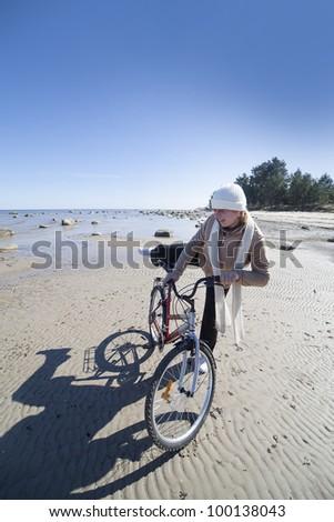 Woman and bicycle at sea.