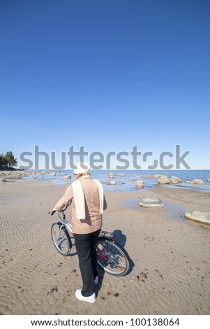Woman and bicycle at sea. - stock photo