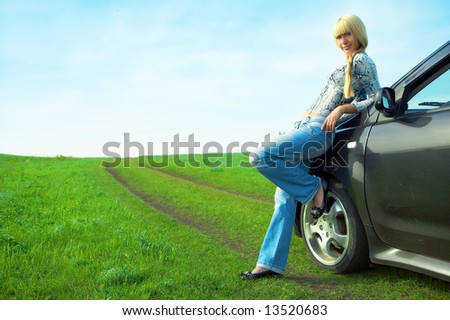 woman and car  on road in green field