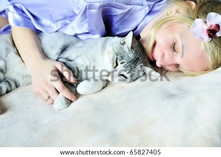 woman and cat playing on the bed