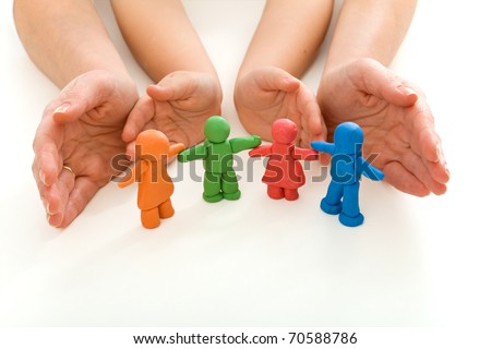 Woman and child hands protecting colorful modeling clay people  family on white background