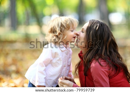Woman and child having fun in autumn park - stock photo