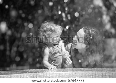 Woman and child having fun near fountain