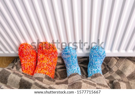 Woman and child wears wool socks warming cold feet with warm blanket in front of heating radiator in winter time. Electric or gas heater at home. The symbolic image of the heating season. #1577715667