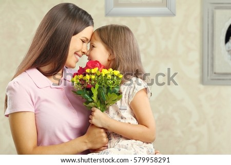 Woman and child with bouquet of flowers. #579958291