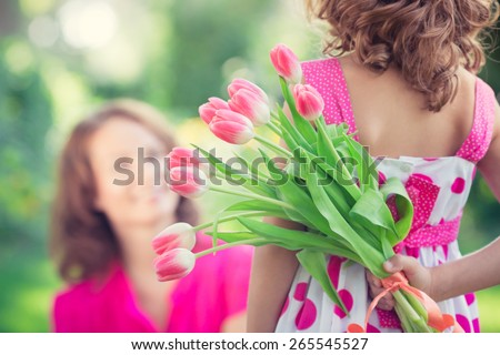 Woman and child with bouquet of flowers against green blurred background. Spring family holiday concept. Women\'s day
