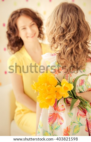 Woman and child with bouquet of flowers at home. Spring family holiday concept. Mother's day #403821598