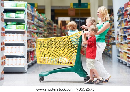 woman and children with shopping cart in supermarket store warwehouse
