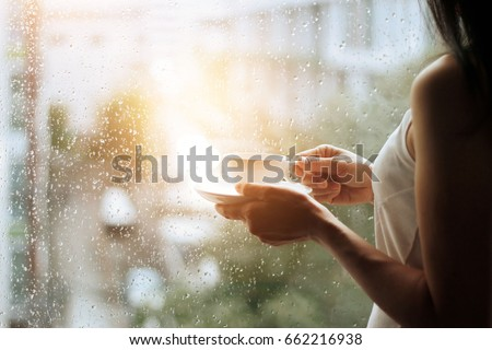 Stock Photo woman and coffee in hands looking through the glass window with a rain drops on city background