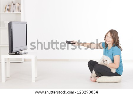 Woman and cute white maltese dog watching TV together at home - stock photo