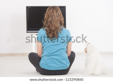 Woman and cute white maltese dog watching TV together at home