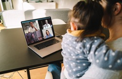 Woman and daughter at home having a video conference with her family and friends. Woman talking with her friends over internet.