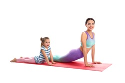 Woman and daughter doing yoga together on white background. Home fitness