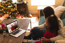 Woman and daughter sitting on couch having a videocall with couple in santa hats smiling on laptop at home. social distancing during christmas festivity quarantine lockdown concept.