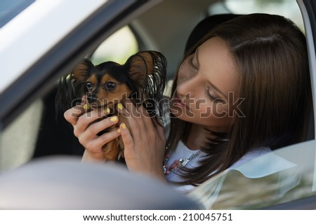 Woman and dog in car on summer travel. Funny dog traveling. Vacation with pet concept.