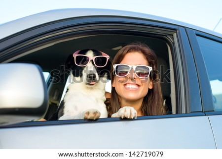 Woman and dog in car on summer travel. Funny dog with sunglasses traveling. Vacation with pet concept.