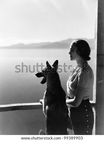 Woman and dog looking out over water