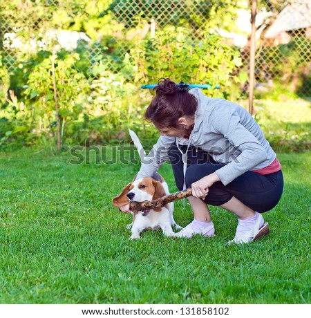 woman and dog plays with a stick on a lawn