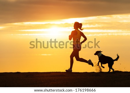 Woman And Dog Running Free On Beach On Golden Sunset. Fitness Girl And Her Pet Working Out Together.