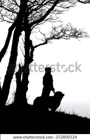 woman and dog silhouettes under trees, monochrome