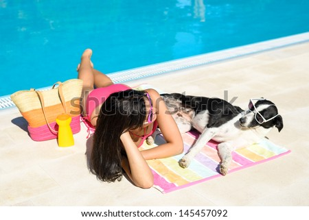 Woman and dog sunbathing together on funny summer at swimming pool like if they were talking to each other. Beautiful girl and her pet wearing sunglasses and having fun on holidays at poolside.