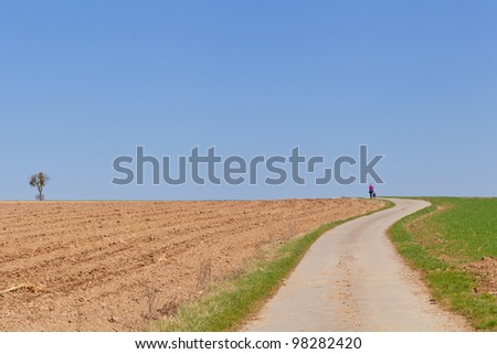 Woman and dog walking on a countryside street